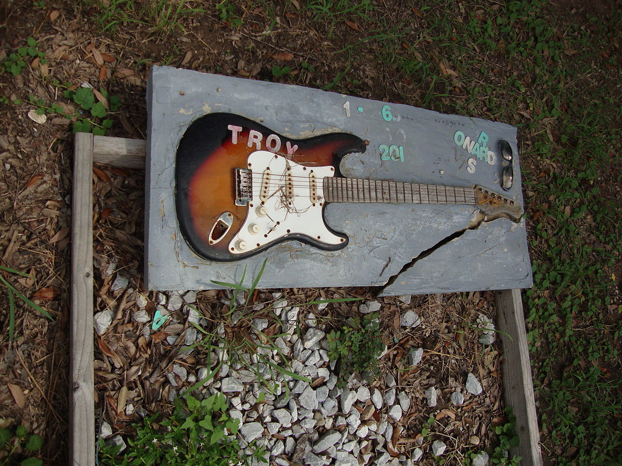 "Grave in Holt Cemetery for ""Troy"" includes the deceased's guitar. (Courtesy Mark Ghstol)"