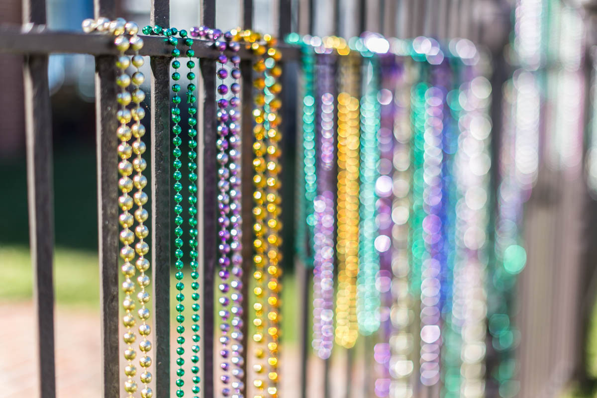 Mardi Gras beads on fence