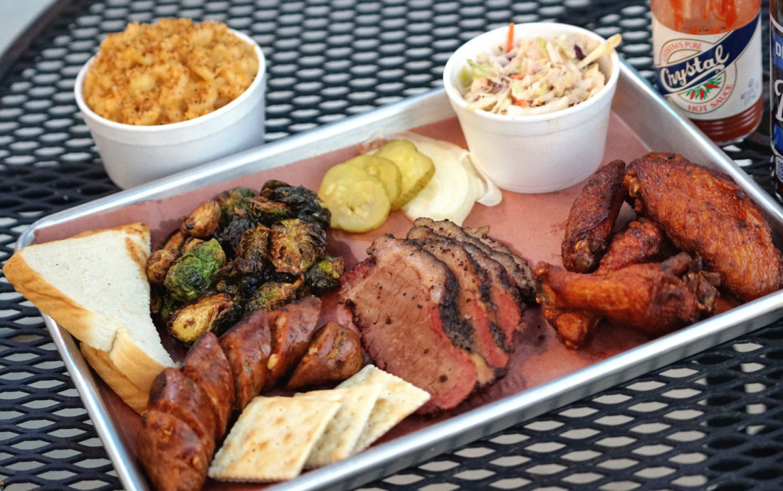 A platter from Blue Oak BBQ with the house spicy green onion sausage, brisket, chicken, cole slaw, mac and cheese, and some addictive fried brussels sprouts.