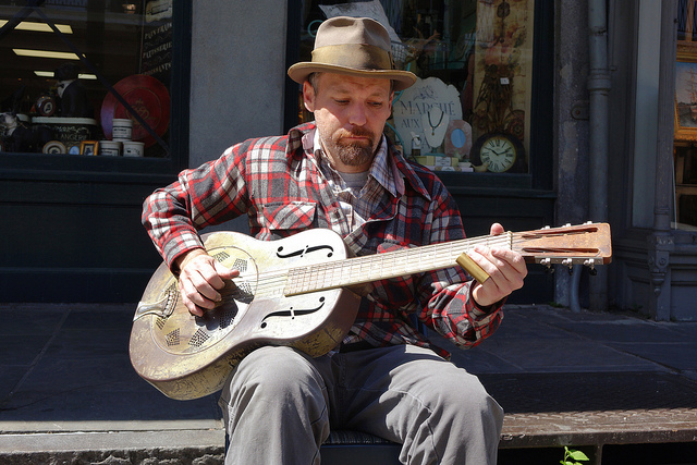 A street musician strumming the blues on Royal Street