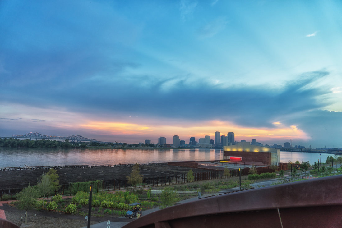 """Perhaps my favorite views at sunset are all from Crescent Park in Bywater and Marigny. This riverfront park, with its modern landscaping is the best place to watch the sunset in fall and winter. The park is only open until 7 PM so fall, winter and early spring are the times of year to plan a visit to catch a sunset before the sun sets any later. This is the view from on top the """"Rusty Rainbow"""" -- the bridge and entrance to Crescent Park at Piety Street and Chartres Street in the Bywater. The glowing red wall in the distance provides an excellent, more close-up view of the downtown skyline. What I love most about the views from Crescent Park is it's the only way to see both the downtown buildings and the bridges on nearly the same plane. The river somehow feels calmer from this vantage point in the park. The views from near the Mandeville Street entrance to the park are also lovely."""