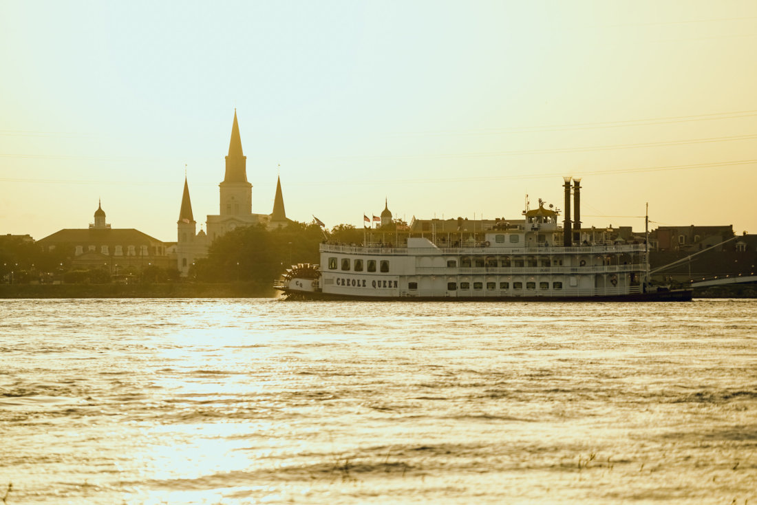 Near the ferry terminal at Algiers Point on the West Bank of New Orleans, there's a perfect view of Jackson Square and you can easily see St. Louis Cathedral. While yes, you can take the ferry and be on the water for a closer-up view of Jackson Square during sunset, timing that is tricky. If you've got a decent telephoto lens on your camera, you can take your time and capture an image similar to this from the riverbank near the ferry terminal at Algiers. It helps that the riverboats are frequently passing in front of the cathedral as the sun is setting.