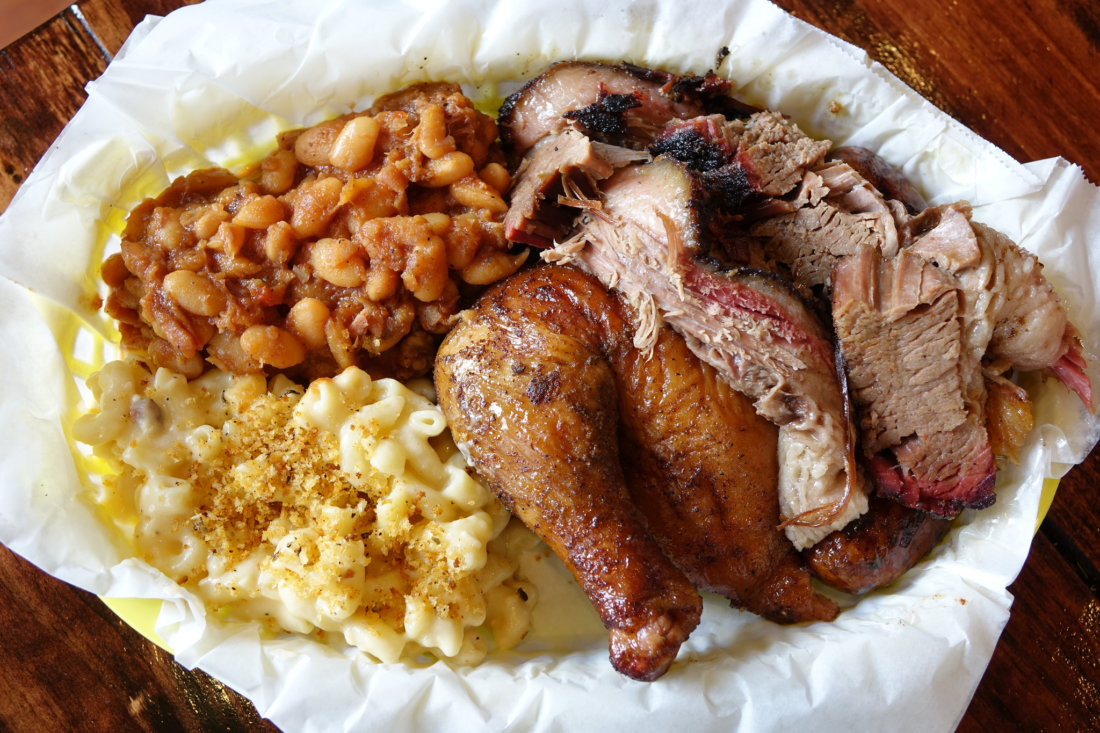 A platter with smoked chicken and brisket with baked beans, mac and cheese from McClure's BBQ, inside the NOLA Brewery on Tchoupitoulas St.
