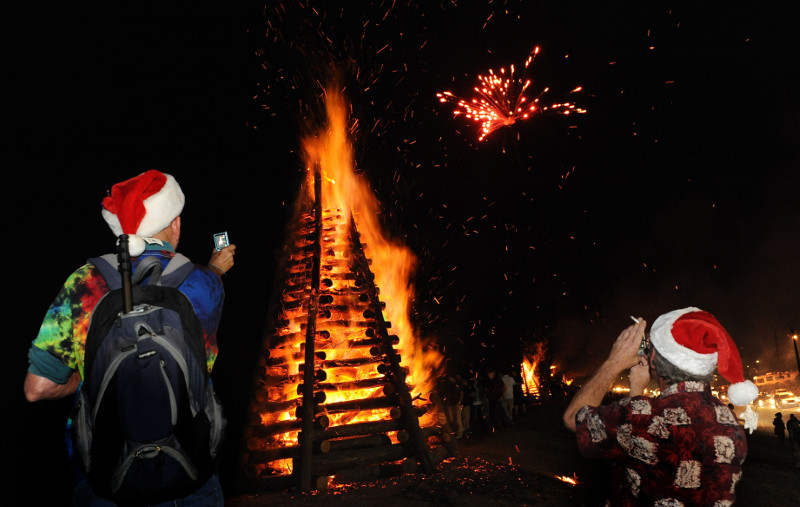 Santa's helpers snap pictures of a Christmas Eve bonfire. (Courtesy photo)