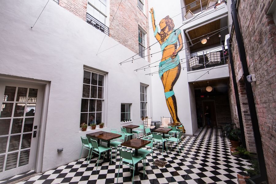 The Courtyard At Catahoula Hotel Features A Larger Than Life Mural Of Local