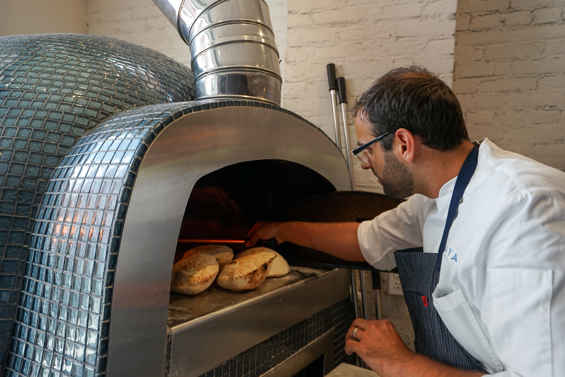 """Shaya bakes pita in a large oven that came at the expense of three extra tables. """"That's what needed to happen in order for us to make the best pita bread we could,"""" he says. (Photo: Paul Broussard)"""